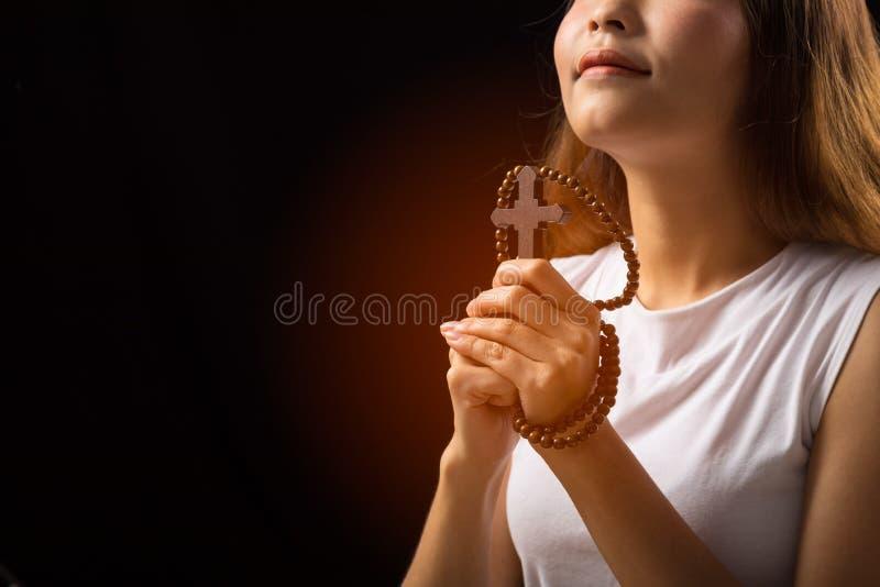 Vrouw bidden tot God met Kruis op zwarte achtergrond; Vrouw Pray voor God zegen stock afbeeldingen