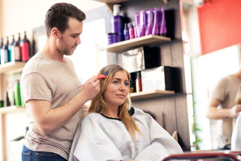 Vrouw bij beuty salon die de behandeling van de haarkleur doen stock foto