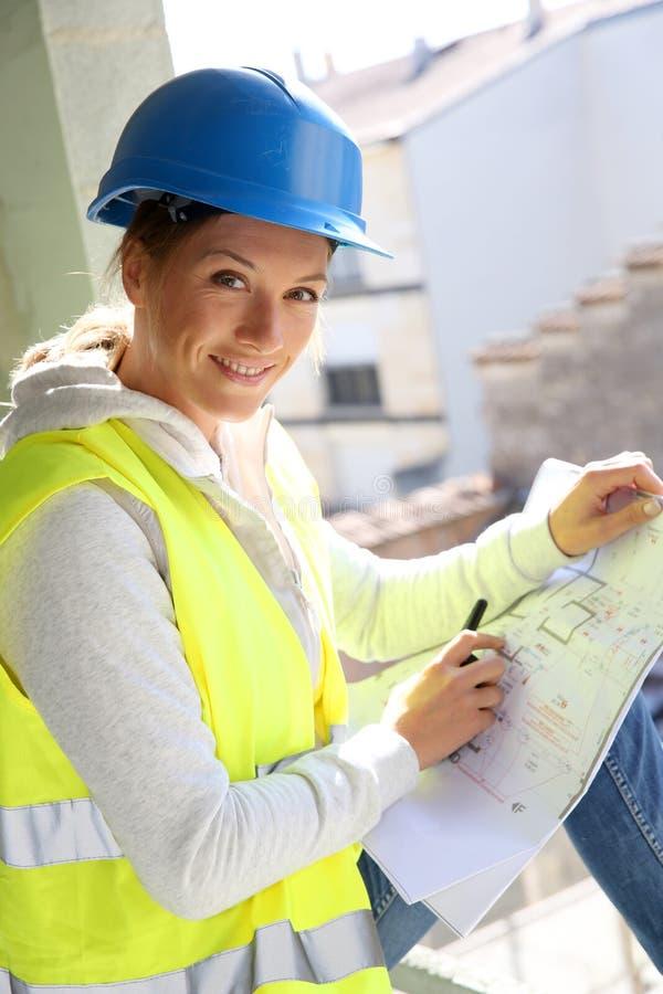 Vrouw bij bouw de bouw het werken stock afbeelding