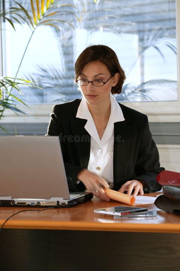 Vrouw bij bureau met laptop computer stock afbeeldingen