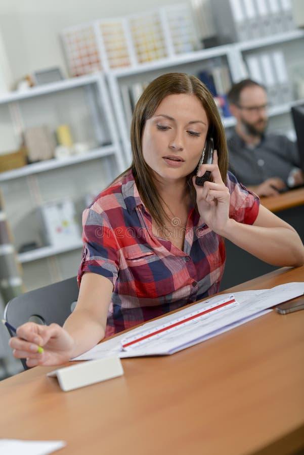 Vrouw bij bureau op telefoon wordt gezeten die stock fotografie