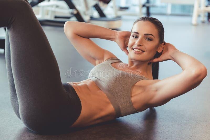 Vrouw bij de gymnastiek stock foto's
