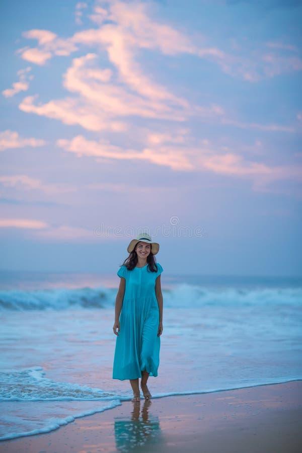 Vrouw bij de kust van Indische Oceaan na zonsondergang stock foto's