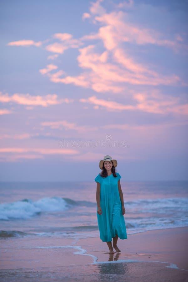 Vrouw bij de kust van Indische Oceaan na zonsondergang stock foto