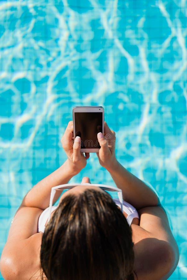 Vrouw bij de zomervakantie het texting op smartphone in zwembad stock afbeeldingen