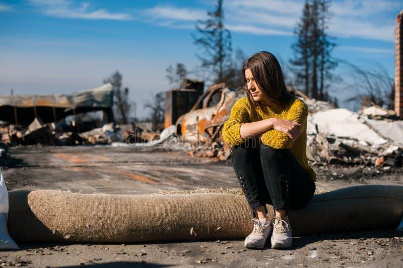 Vrouw bij gebrande geruïneerde huis en werf, na brandramp royalty-vrije stock afbeelding