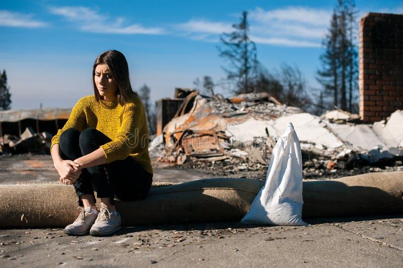 Vrouw bij gebrande geruïneerde huis en werf, na brandramp stock afbeelding