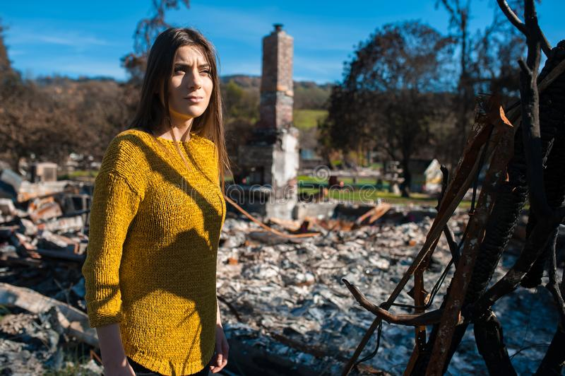 Vrouw bij gebrande geruïneerde huis en werf, na brandramp stock afbeeldingen