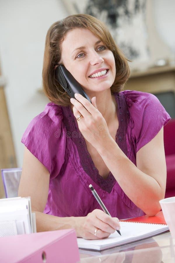 Vrouw bij haar bureau dat op telefoon spreekt stock fotografie