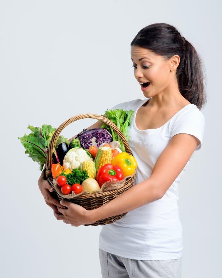 Vrouw bij haar gezonde mand van groenten wordt geschokt die stock foto
