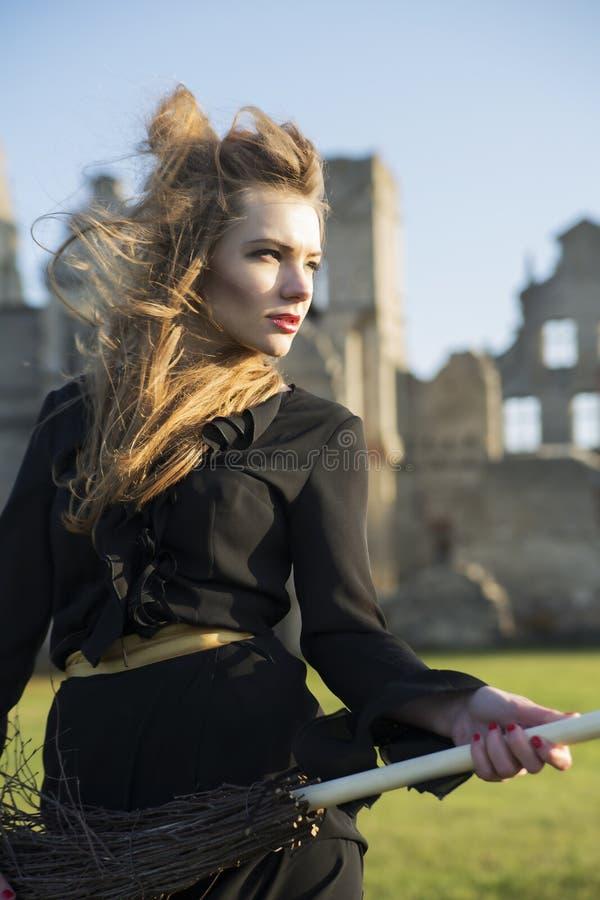 Vrouw bij heksenkostuum op ruïnesachtergrond stock foto