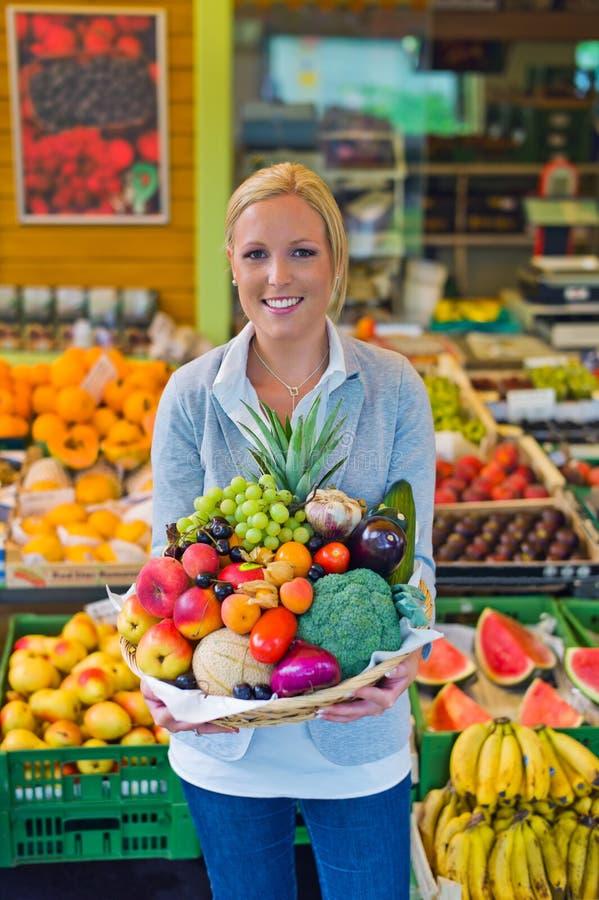 Vrouw bij het fruit en de plantaardige markt stock afbeeldingen