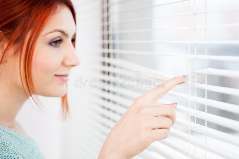 Vrouw bij het venster die door de jaloezie kijken stock foto