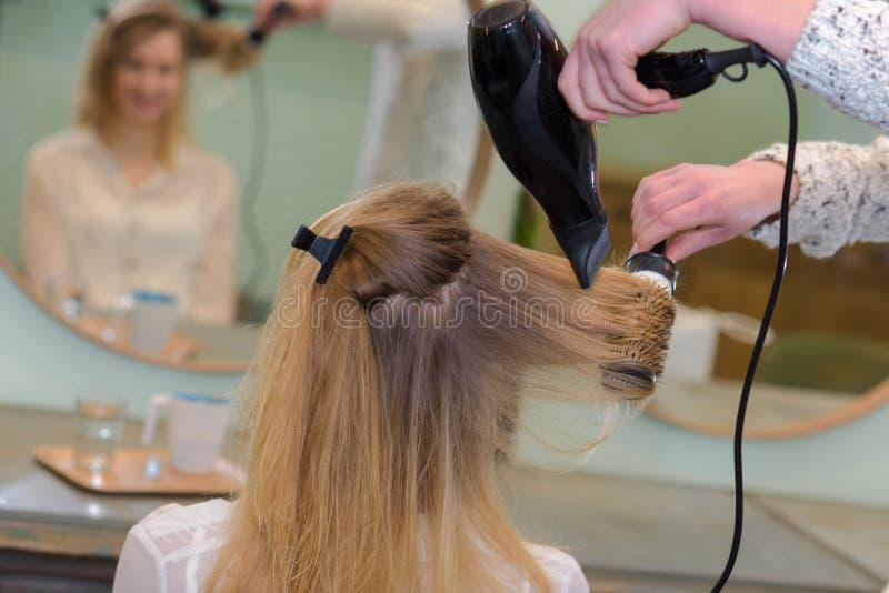 Vrouw bij kapper die haarborstel hebben royalty-vrije stock fotografie