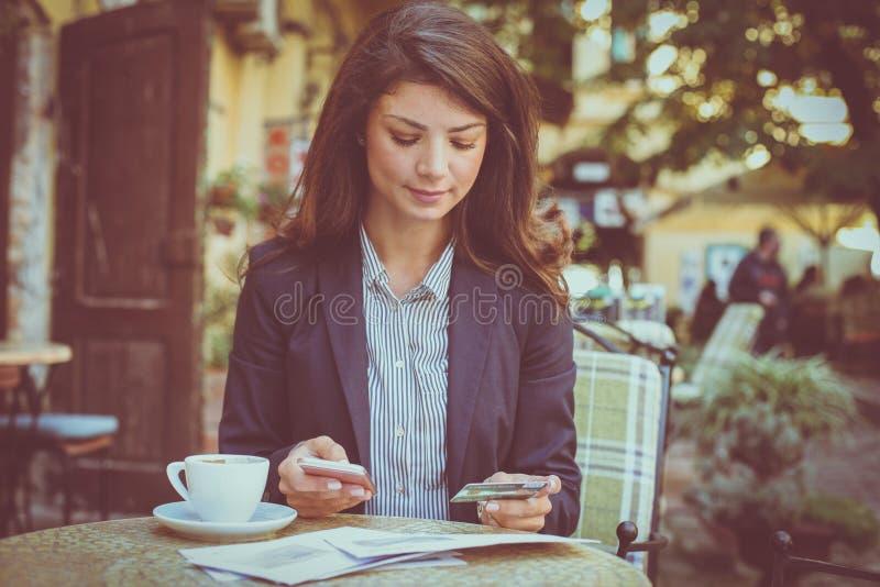 Vrouw bij koffie, die telefoon met behulp van aan controlecreditcard stock afbeeldingen
