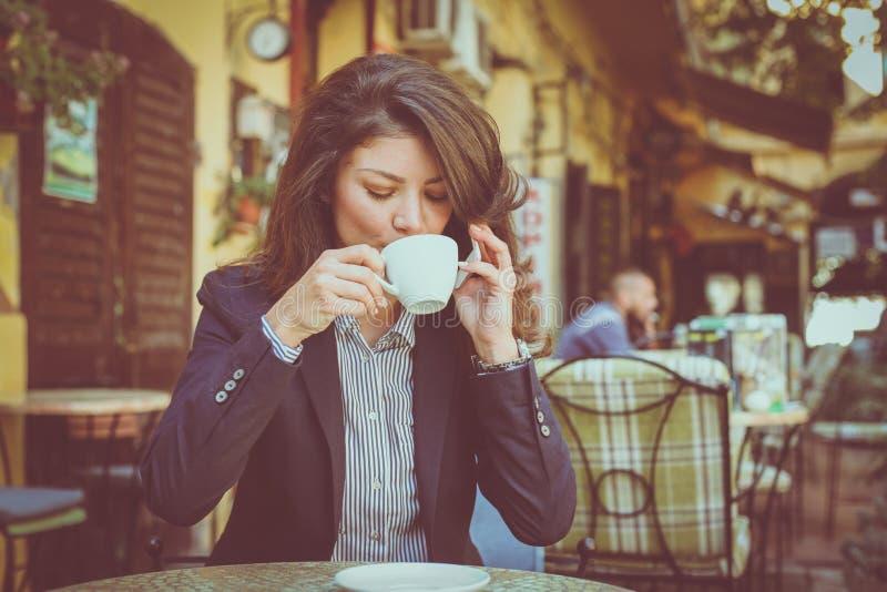 Vrouw bij koffie het drinken koffie en het spreken op telefoon royalty-vrije stock fotografie