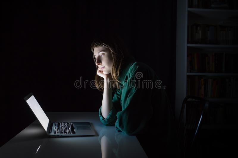 Vrouw bij laptop computer laat in de bored avond of lezing stock fotografie