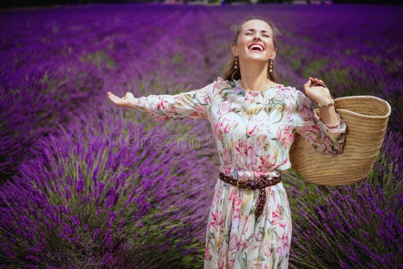 Vrouw bij lavendelgebied met zich strozak het verheugen stock afbeelding