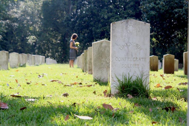 Vrouw bij Onbekend militair` s graf met gele bloemen stock fotografie