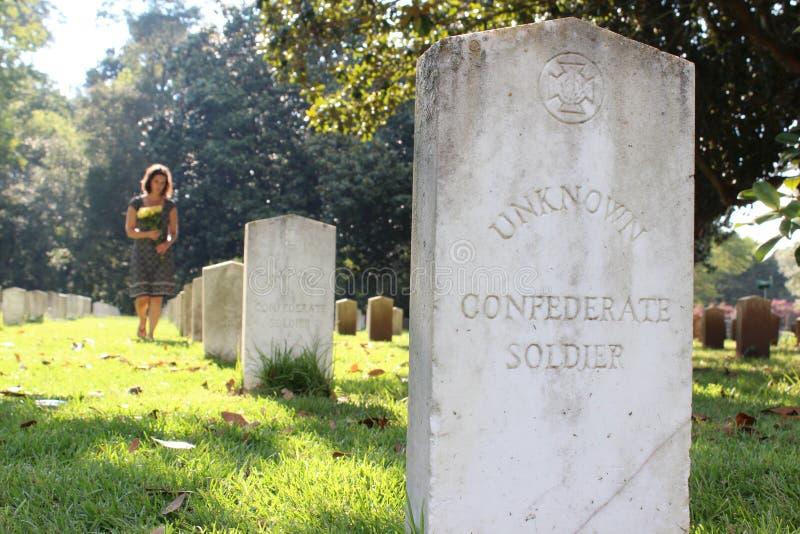 Vrouw bij Onbekend militair` s graf met gele bloemen stock foto