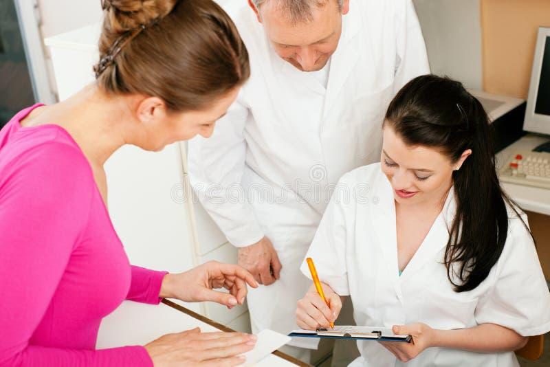 Vrouw bij ontvangst van kliniek stock afbeeldingen