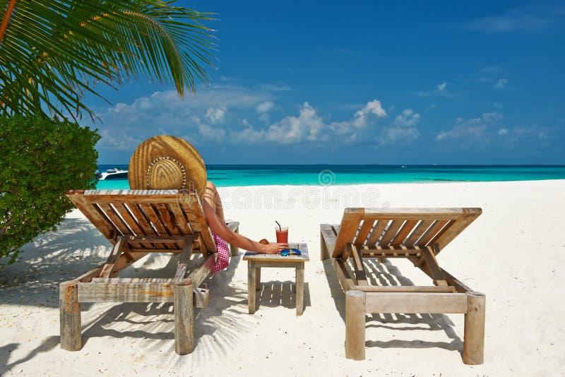 Vrouw bij strand met chaise-zitkamers stock foto