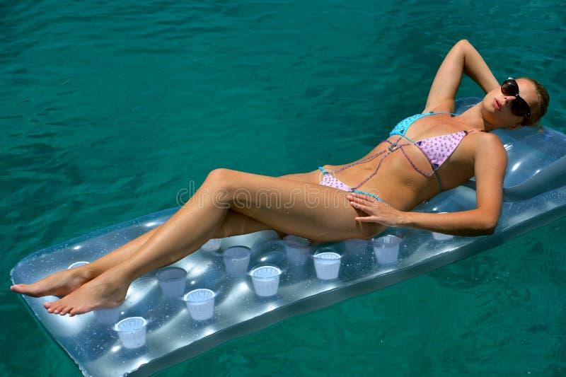 Vrouw in bikini die op drijvend apparaat zonnebaden stock afbeelding