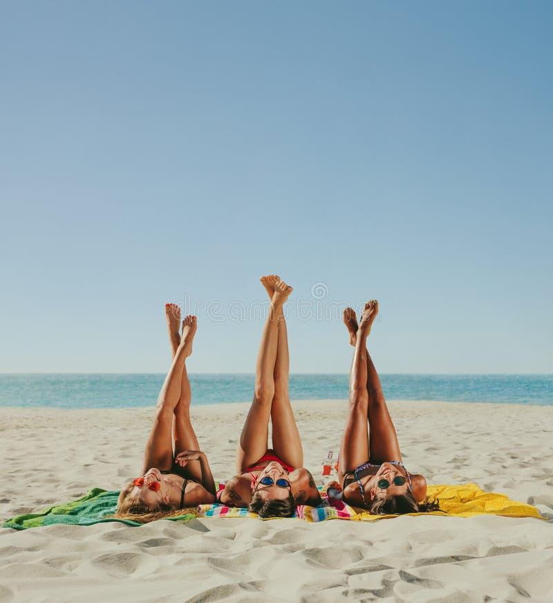 Vrouw in bikini die die op strand met benen zonnebaden aan de hemel worden opgeheven royalty-vrije stock foto's