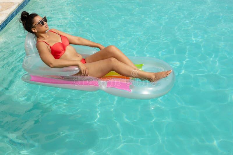 Vrouw in bikini het ontspannen op een opblaasbare buis in zwembad bij de binnenplaats van huis stock afbeelding