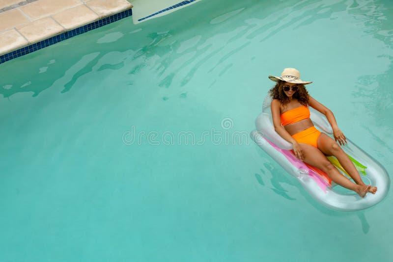 Vrouw in bikini het ontspannen op een opblaasbare buis in zwembad bij de binnenplaats van huis stock foto's