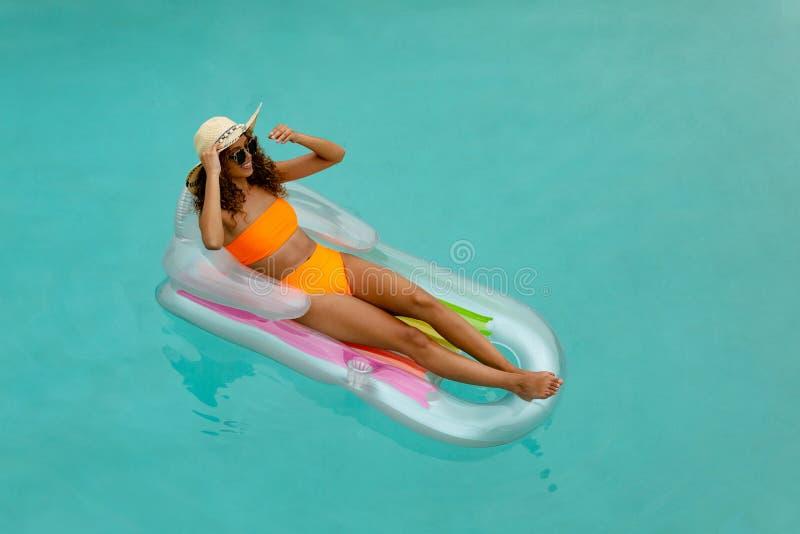 Vrouw in bikini het ontspannen op een opblaasbare buis in zwembad bij de binnenplaats van huis stock afbeeldingen