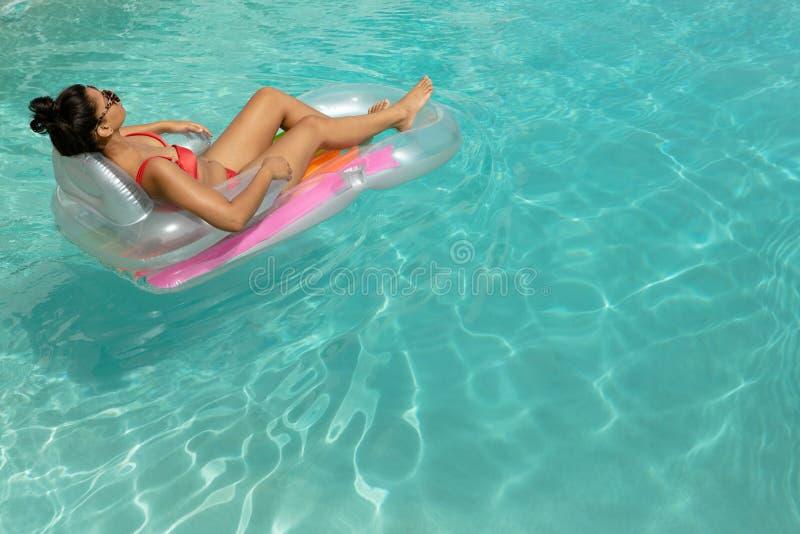 Vrouw in bikini het ontspannen op een opblaasbare buis in zwembad bij de binnenplaats van huis stock fotografie