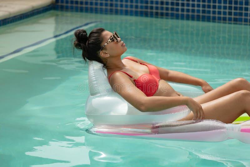 Vrouw in bikini het ontspannen op opblaasbare buis in zwembad bij de binnenplaats van huis stock foto's