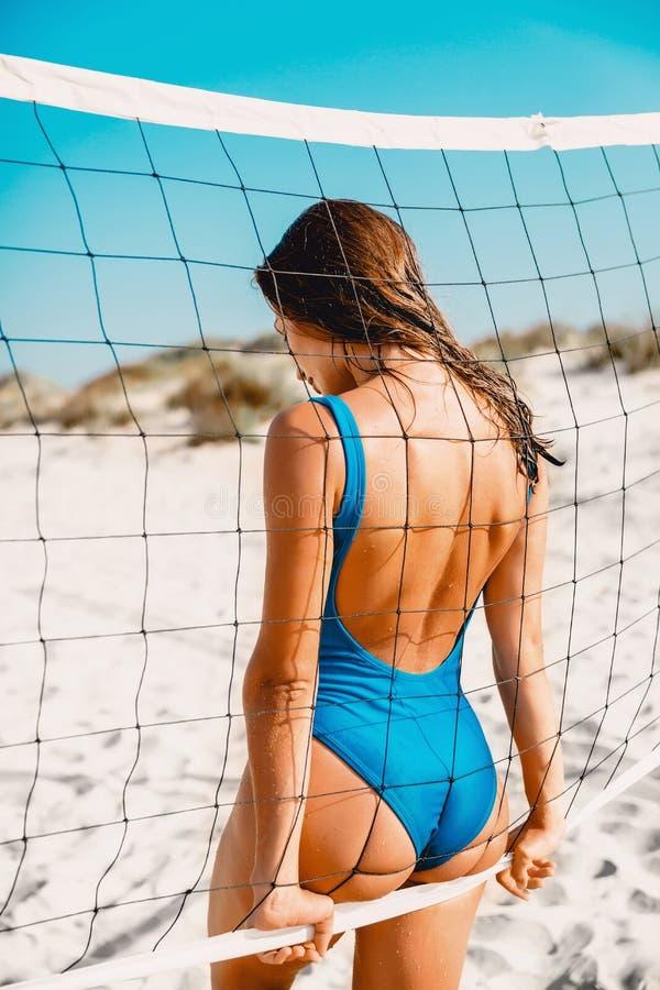 Vrouw in bikini met tennis netto op tropisch wit zandstrand in Australië Het geschikte lichaam van de de zomervrouw royalty-vrije stock afbeeldingen