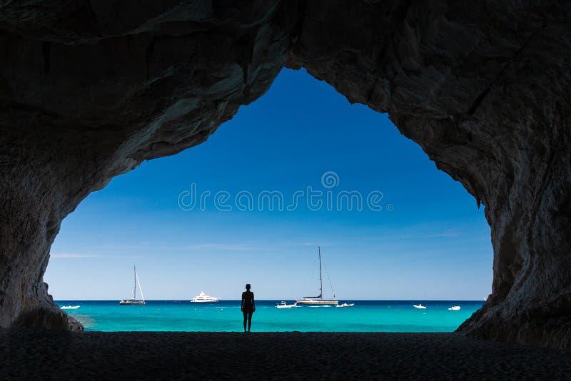 Vrouw binnen een hol bij Cala Luna strand stock foto's