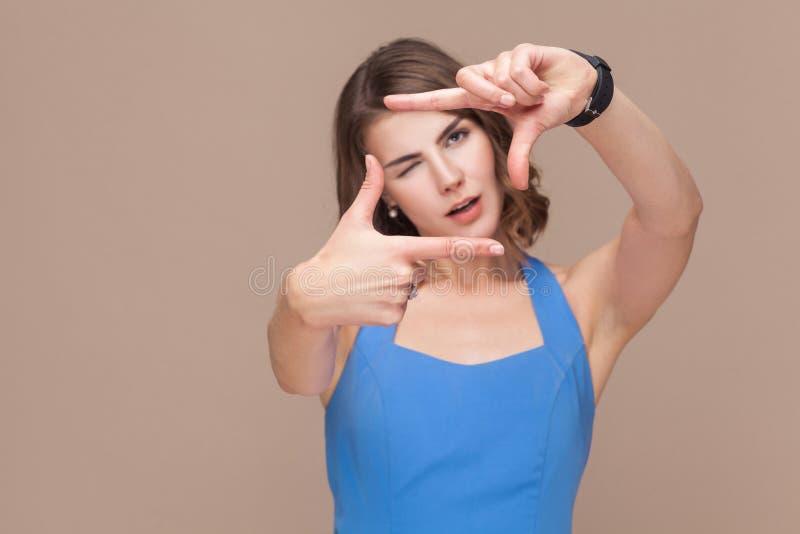 Vrouw in blauwe kleding die perspectiefkader of gewas tonen stock foto