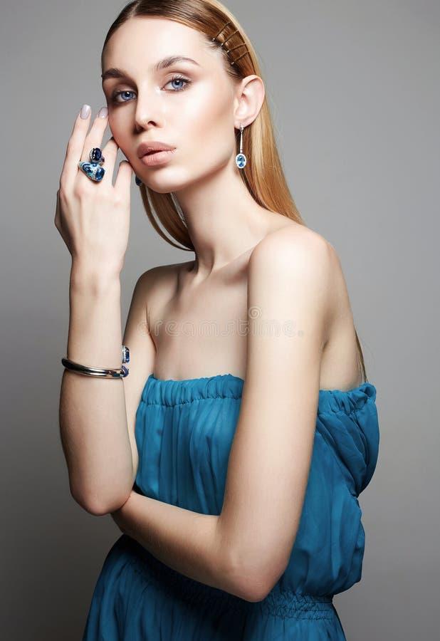 Vrouw in blauwe kleding en juwelen juwelen op mooi meisje stock afbeelding