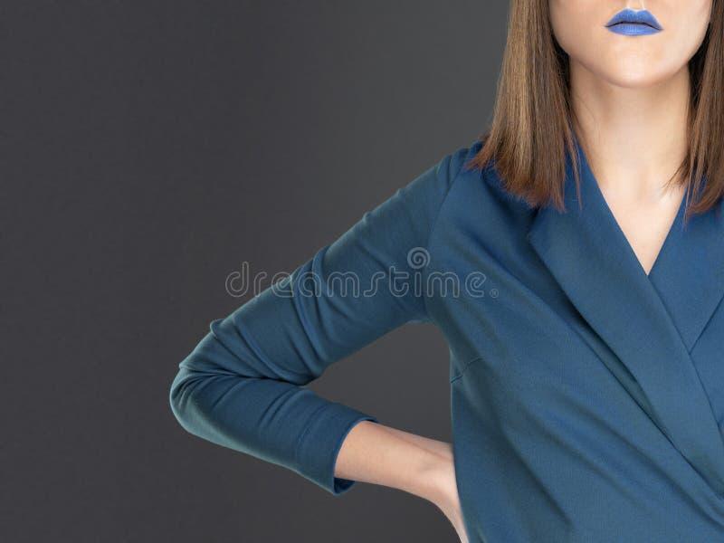 Vrouw in blauwe kleding met blauwe lippenstift op lippen stock afbeelding