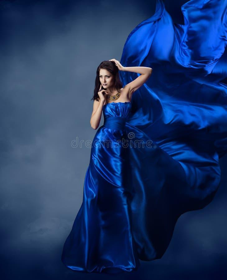 Vrouw in blauwe kleding met vliegende zijdestof stock fotografie