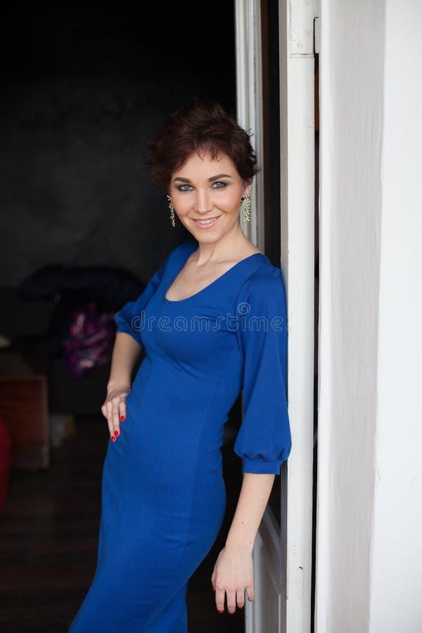 Vrouw in blauwe kledingstribunes tegen de muur royalty-vrije stock fotografie