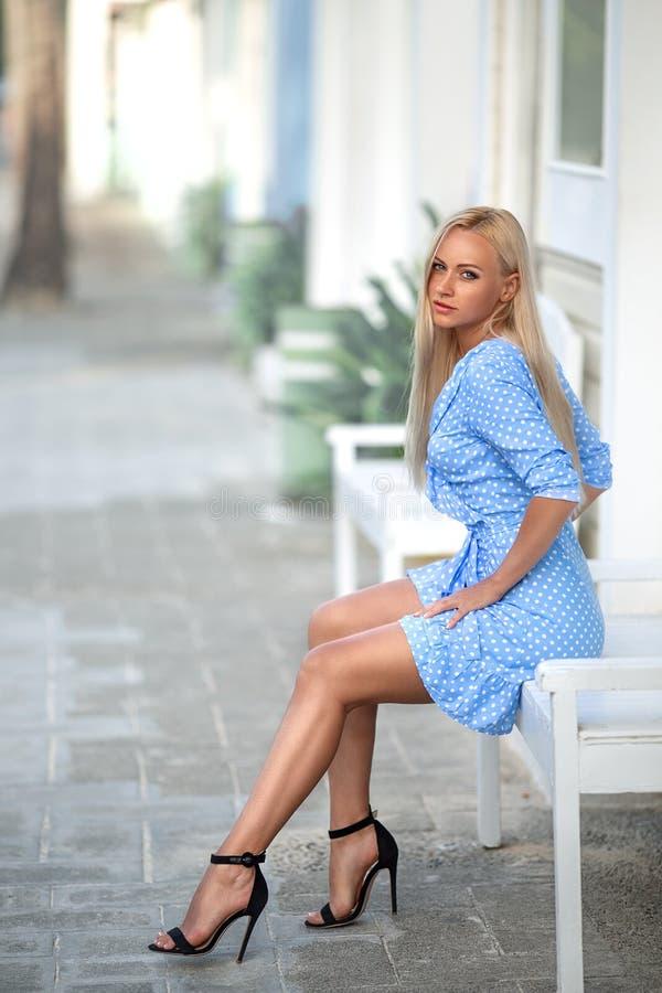 Vrouw in blauwe kledingszitting op de bank stock afbeeldingen