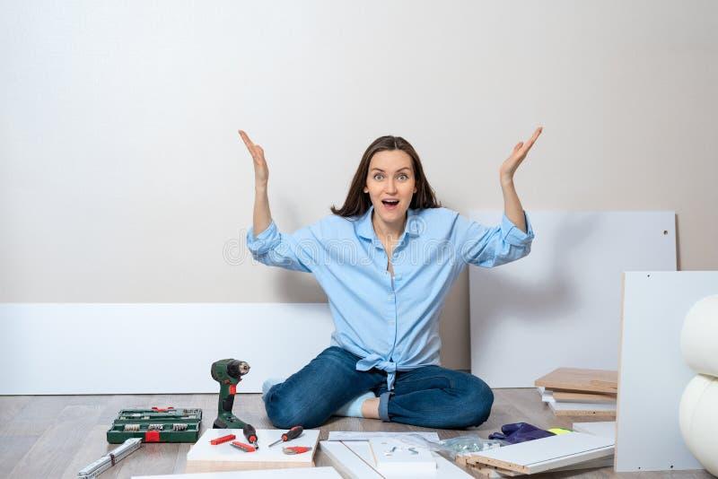Vrouw in blauwe overhemdszitting op de vloer met hulpmiddelen om meubilair te assembleren royalty-vrije stock afbeeldingen
