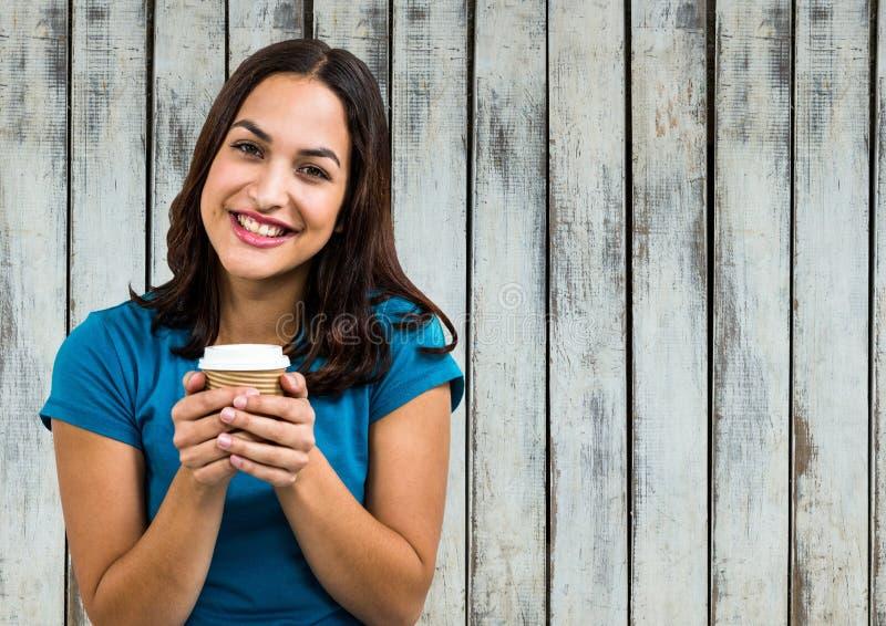 Vrouw in blauwe t-shirt met koffiekop tegen houten paneel royalty-vrije stock afbeelding