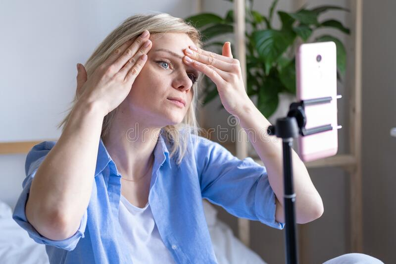 Vrouw-blogger die met volgers praat, live streaming, op zoek naar een smartphonescherm op bed Maken van gezichtsmaccage royalty-vrije stock fotografie