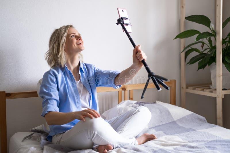 Vrouw-blogger die met volgers praat, live streaming, op zoek naar een smartphonescherm op bed Videogesprek voeren naar royalty-vrije stock fotografie