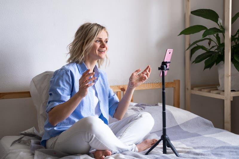 Vrouw-blogger die met volgers praat, live streaming, op zoek naar een smartphonescherm op bed Videogesprek voeren naar stock afbeeldingen