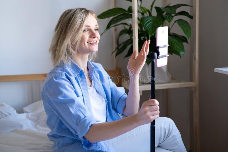 Vrouw-blogger die met volgers praat, live streaming, op zoek naar een smartphonescherm op bed Videogesprek voeren naar royalty-vrije stock afbeelding
