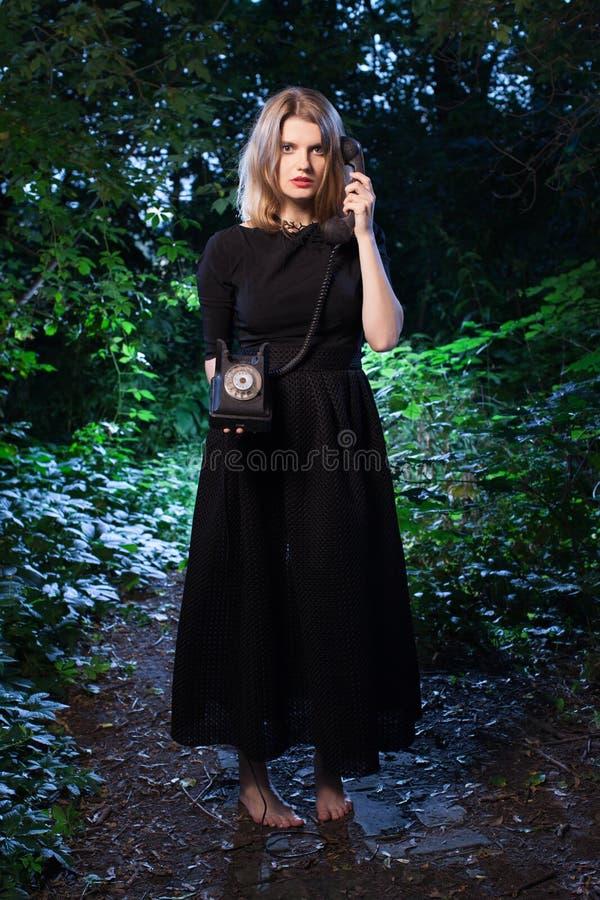Vrouw in bos in dark stock fotografie
