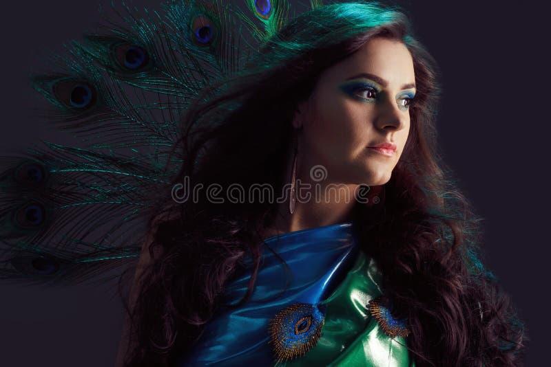 Vrouw in briljante blauwe kleding met het ontwerp van pauwveren Creatieve fantasiemake-up, lang donker haar die bij wind fladdere stock foto