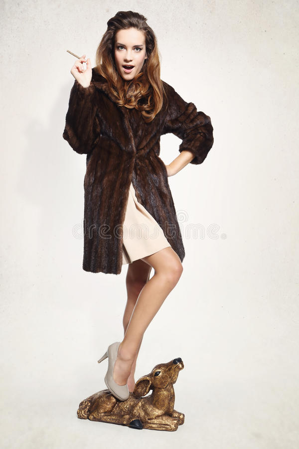 Vrouw in bruine bontjas met fawn royalty-vrije stock afbeeldingen